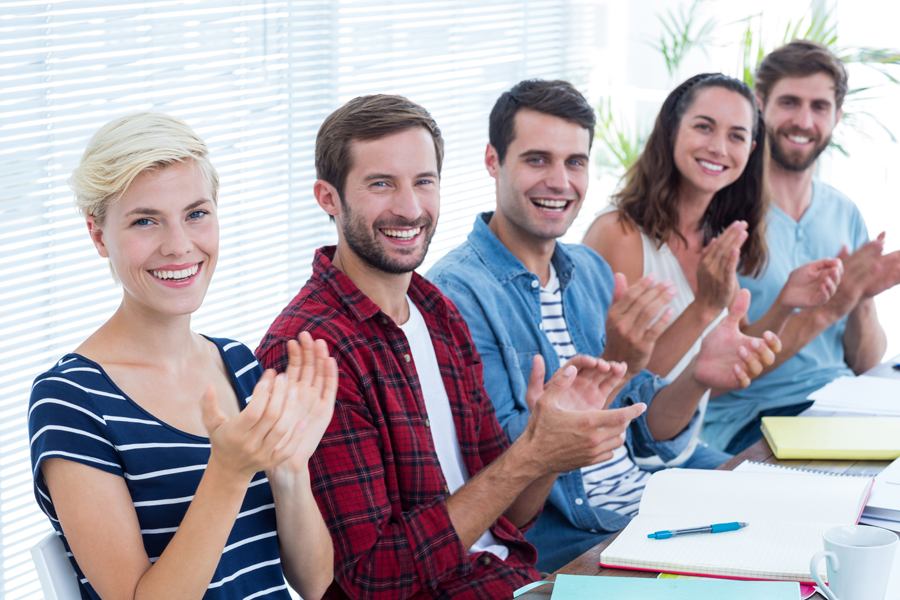 Young smiling business people clapping hands in meeting at the office